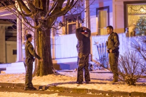 Border Patrol Agents hold a man while Sheriff's Deputies search a home at 172 South Main Street in Richford on Sunday evening. Photograph By Gregory J. Lamoureux